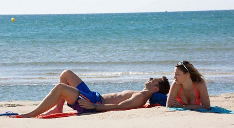 Un couple allongé dans le sable sur une plage