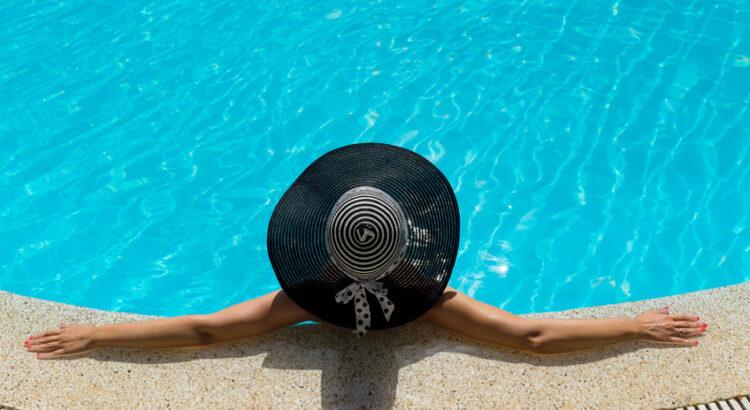 Femme avec un chapeau se relaxant dans une piscine