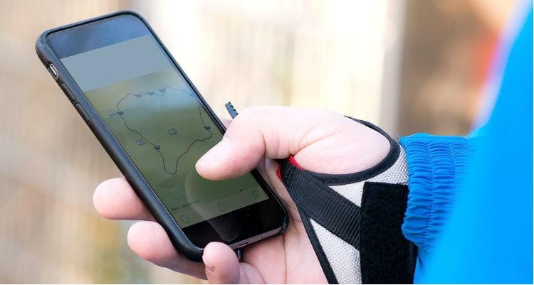 Personne utilisant une application de randonnée sur mobile