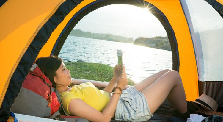 Femme allongée dans une tente regardant son smartphone