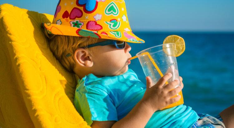 Enfant sur un transat à la plage buvant un jus d'orange